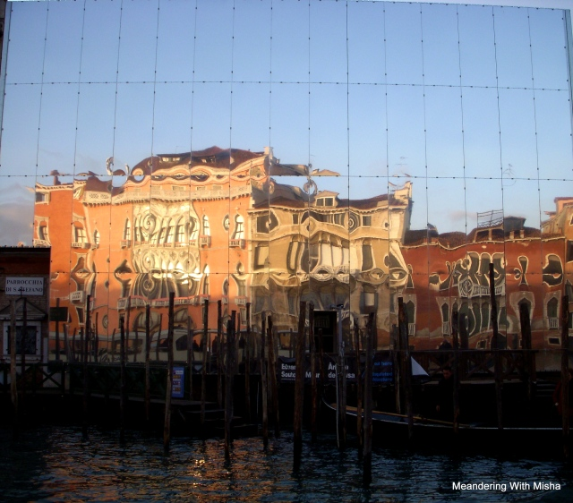 Mirrored scaffolding reflects the palazzo across the Grand Canal